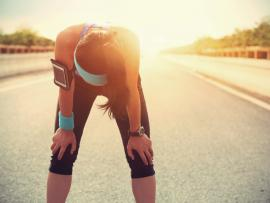 woman bent over after running in heat